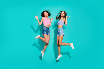 Wall Mural - Full length body size photo jumping beautiful two funky wavy she her ladies hands arms raised in hi gesture friendly wearing shiny jeans denim shorts tank tops isolated teal bright vivid background