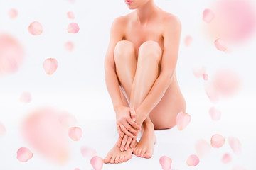 Front view close up photo naked charming woman with perfect body and clean smooth skin after spa sitting on the floor and hugging her knees isolated on white pink background