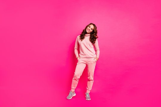 Full length body size photo toothy beaming smiling amazing she her lady hands arms in pockets self-confident wearing modern casual pink costume suit pullover outfit isolated vibrant rose background