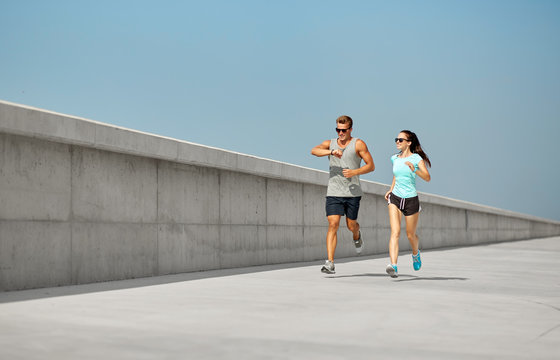 fitness, sport and lifestyle concept - happy couple in sports clothes and sunglasses running outdoors