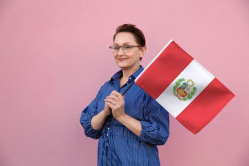 Peru flag. Woman holding Peruvian flag. Nice portrait of middle aged lady 40 50 years old holding a large flag over pink wall background on the street outdoors.