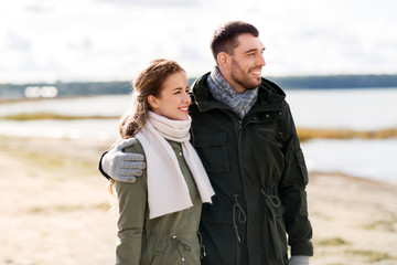 love, relationship and people concept - smiling couple hugging on autumn beach
