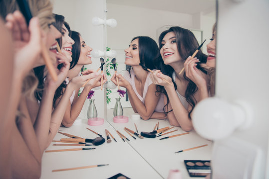 Portrait of nice cute winsome attractive lovely well-groomed glamorous shine cheerful girlfriends having fun blush blusher in light white interior decorated house indoors