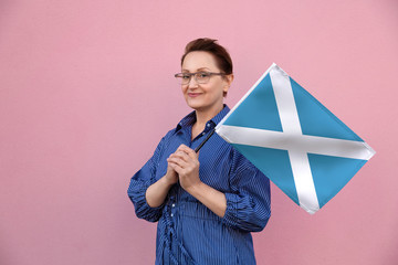 Scotland flag. Woman holding Scottish flag. Nice portrait of middle aged lady 40 50 years old holding a large flag over pink wall background on the street outdoors.