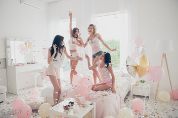 Nice-looking cool crazy careless carefree attractive feminine fit thin slim graceful cheerful funny girlfriends having fun showing v-sign in light white interior decorated house