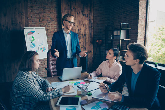 Four nice chic stylish elegant cheerful business sharks experts listening to speaker presenter saying speech at modern industrial loft interior work place station