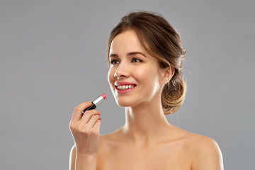 beauty, make up and cosmetics concept - smiling young woman applying pink lipstick over grey background