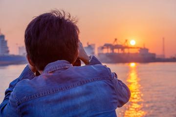 Male photographer taking photo of riverside sunset.