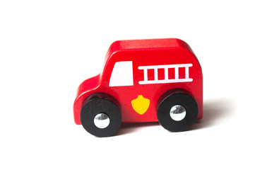 closeup of red  miniature wooden truck on white background - concept fire rescue