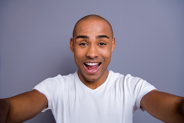 Close up photo funky dark skin he him his macho short hairdo make take selfies video call glad opened mouth cool see relatives friends wearing white t-shirt outfit clothes isolated grey background