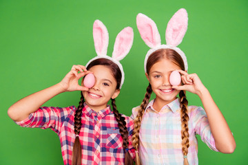 Close up photo of two pretty little age girls holiday concept with bunny ears on head hiding one eye behind easter colored eggs wearing casual checkered plaid shirts isolated on green background