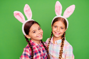 Close-up photo portrait of couple of positive cheerful glad with teeth smile pre teen scholl girls holding painted chocolate eggs looking at camera wear casual plaid shirt isolated vivid background