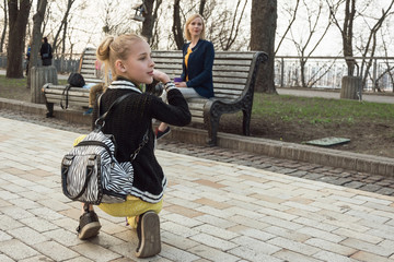 A girl photographs her mother in the park.