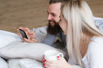 Morning young couple wake up ritual. Bearded man and woman in bed with cup of drink and smartphone.