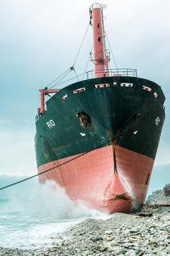 Huge metal vessel located near coast against cloudy blue sky