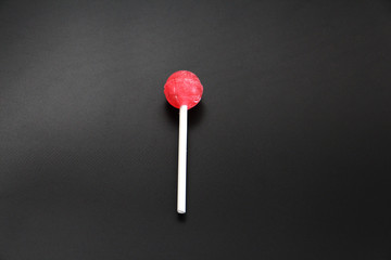 Sweet multicolored caramel on a stick. Sweets laid out on the table. Sweet life on a dark and white background. Caramel is one and many candies are laid out in a circle.
