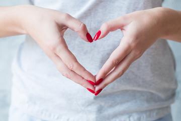 Romantic concept. Woman hands showing love heart symbol.