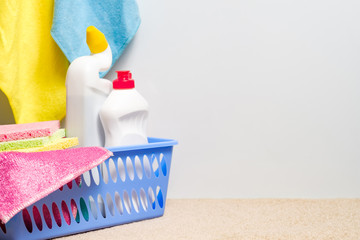 Cleaning products group. Plastic basket with supplies. Copy space on white backdrop.