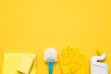Toilet cleaning supplies. Basic cleanup set flat lay. Copy space on yellow background.