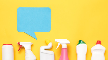 Housekeeping services review. Row of cleaning supplies and detergents . Blue speech bubble on yellow copy space.