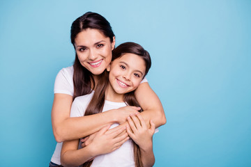 Close up photo amazing pretty two people brown haired mum mom small little daughter stand hugging piggy back lovely free time rejoice wearing white t-shirts isolated on bright blue background Wall mural