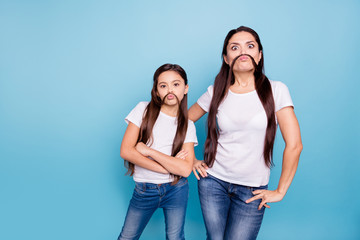 Close up photo beautiful two people brown haired mom small little daughter make moustache curls like guys man male fooling around wear white t-shirts isolated bright blue background Wall mural