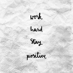 Work hard Stay positive on gray and white crumpled paper