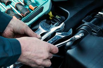 Mechanic repairs car. Wrench in male hand. Car service, engine repair, car repair shop. Wall mural