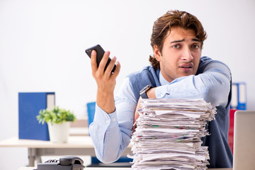 Young handsome employee unhappy with excessive work