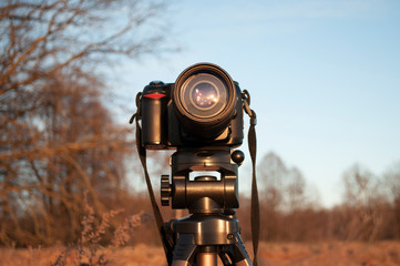 DSLR camera on a tripod against the forest and sky, sun glare reflected in the lens, early spring photo landscape