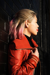Edgy portrait of Asian woman wearing a red coat and red lips against a black brick wall
