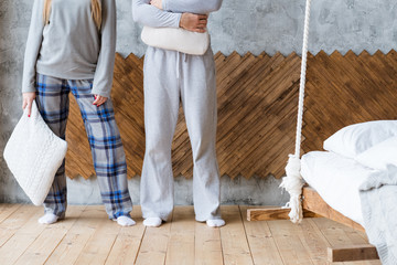 Good morning. Young couple standing by wall with pillows. New day ahead.