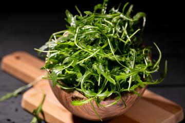 Fresh rocket salad in bowl on the wodden background