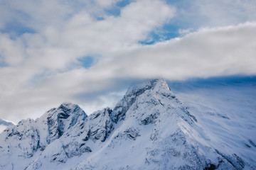 mountain peaks of Dombai mountains covered with snow surrounded by thick clouds against the blue sky