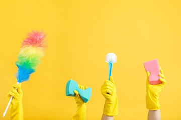 Housekeeping and cleaning services. Hands in rubber gloves holding cleanup supplies. Copy space on yellow background.