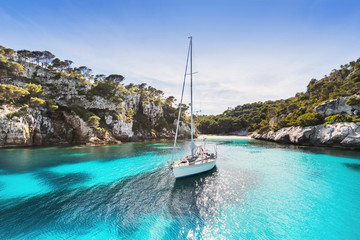 Beautiful beach with sailing boat yacht, Cala Macarelleta, Menorca island, Spain. Yachting, travel and active lifestyle concept Wall mural
