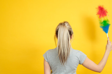 Early spring regular cleanup. Woman with feather duster backview. Copy space on yellow background.