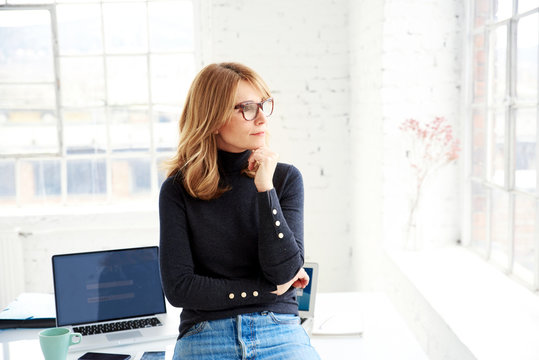 Portrait of casual businesswoman deep in thought while standing in the office