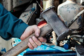 Male hand holding big hammer, sledgehammer. Repairing tractor engine. Mechanic repairing tractor.