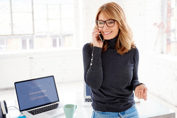 Happy businesswoman talking with somebody on her mobile phone while standing in the office