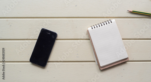 Wall mural Working space, notebook, and smart phone  on white wooden desk