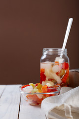 Marinated various vegetables in a glass jar on white wooden background.