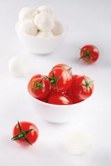 Fresh cherry tomatoes and mozzarella on white background