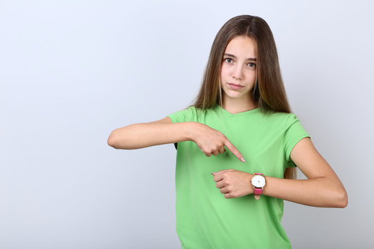 Young girl with wrist watch on grey background