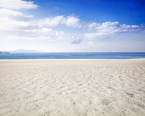 Beach background of yellow sand and sea landscape with blue sky. Free space for your decoration.