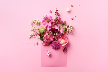 Pink envelope with spring flowers. Floral composition, creative layout. Flat lay, top view. Spring, summer or garden concept. Present for Woman day