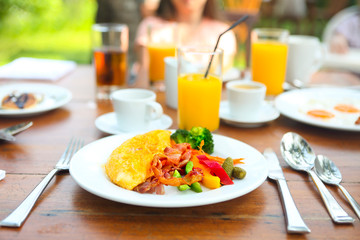 Omelet with pepper, cucumber, bakon and salad on the table