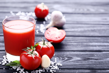 Wall Mural - Tomato juice in glass with garlic and salt on black wooden table
