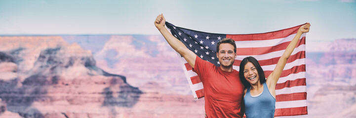 USA flag american travel tourists people holding flag in Grand Canyon banner background. Happy young interracial couple cheering during summer holidays.
