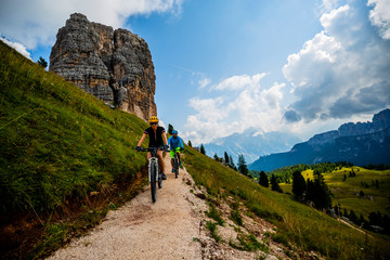Couple cycling in Cortina d'Ampezzo, stunning Cinque Torri and Tofana in background. Woman and man riding MTB trail. South Tyrol province of Italy, Dolomites.